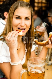 Girl drinking beer and eating bretzel at Oktoberfest Stock Photo