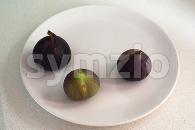 Purple figs on a white plate Stock Photo