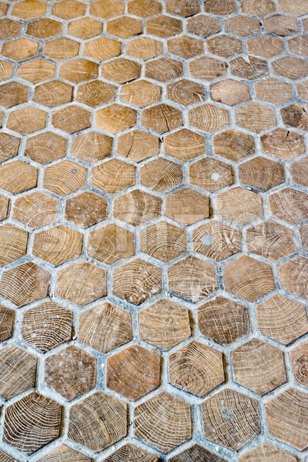 Elaborated old wooden floor made of wooden hexagon tiles and concrete