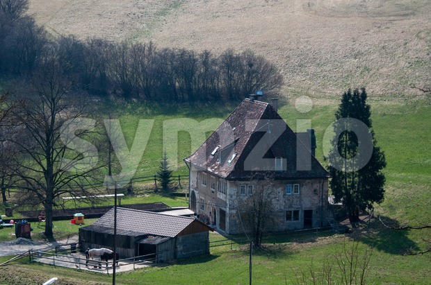 A large old farmhouse with horses and stable surrounded by fields and meadows
