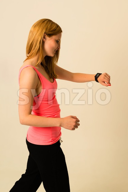 KIRCHHEIM, GERMANY - MAY 23, 2015: An attractive young woman is checking her Apple Watch displaying the activities screen whilst ...