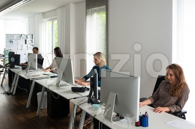 Young team working at desks in stylish office Stock Photo