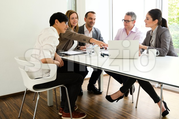 Asian man participating in a business meeting with caucasian colleagues in beautiful environment, might be a startup company