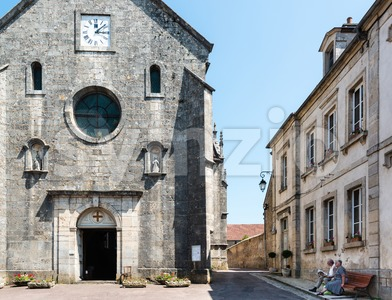 Senior couple sitting on a bench in front of the church of Flavigny-Sur-Ozerain, France Stock Photo