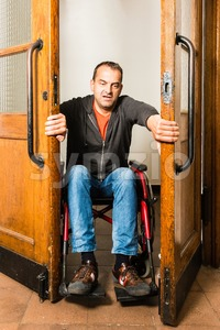 Man in wheelchair stuck between swing doors Stock Photo