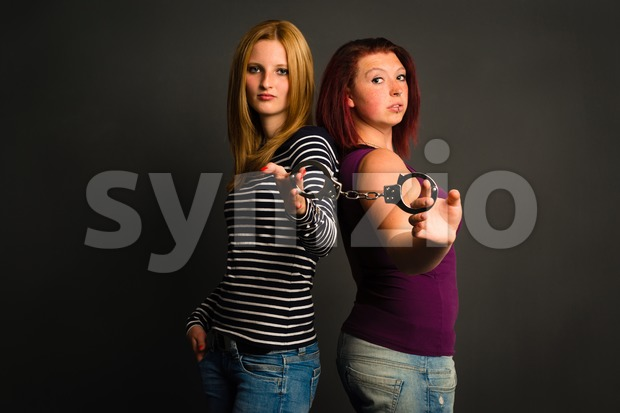 two young women with handcuffs Stock Photo