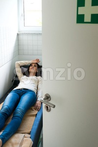Young woman is relaxing in a quiet room of an office Stock Photo