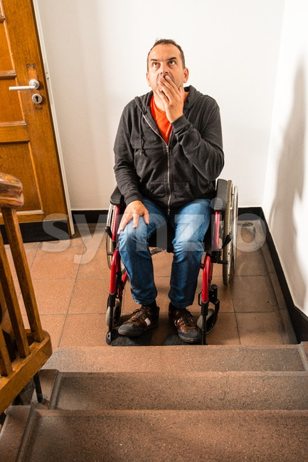 man in wheelchair facing a barrier of stairs Stock Photo