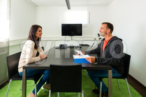 Young female candidate talking during job interview Stock Photo