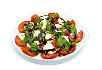 Tomato and mozzarella with basil leaves on a plate Stock Photo