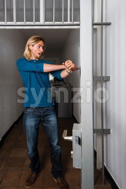 Tied to the office - Young handsome casual business guy  is strapped to metal office doors with handcuffs - ...