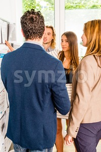 Businesspeople looking at bulletin board in office Stock Photo