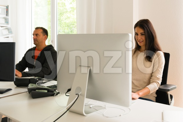 Office people being absorbed in their work: Attractive young woman working in front of her modern bright computer screen with ...