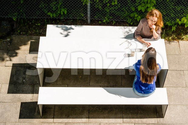 Two businesswomen having a coffee break on office terrace outdoor drinking coffee and talking as seen from above