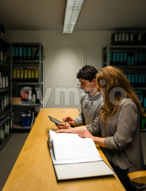 digitalization: young man and woman in the company archives Stock Photo