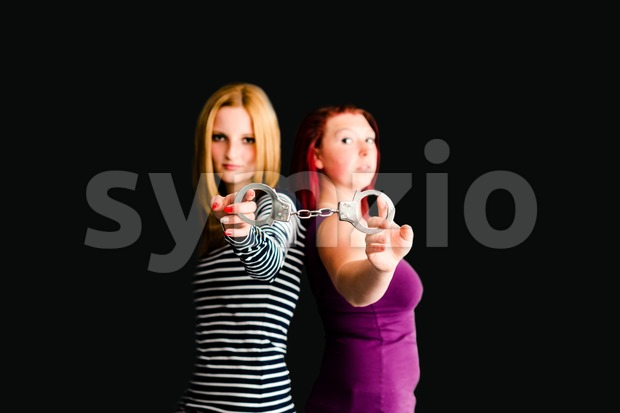 Portrait of two young teenage friends looking tough while holding handcuffs against gray background - shallow depth of field