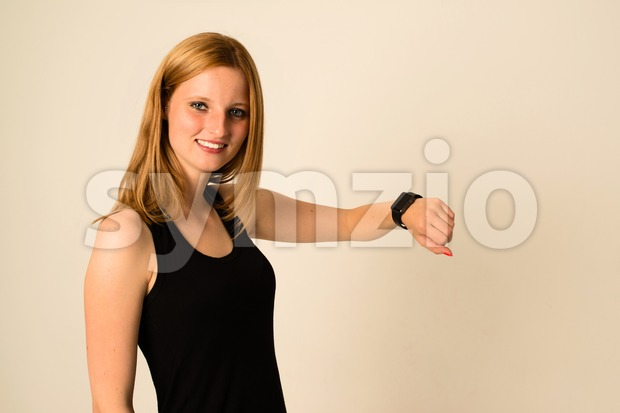 Kirchheim, Germany - May 23, 2015: An attractive young woman is looking into the camera wearing her Apple Watch displaying ...