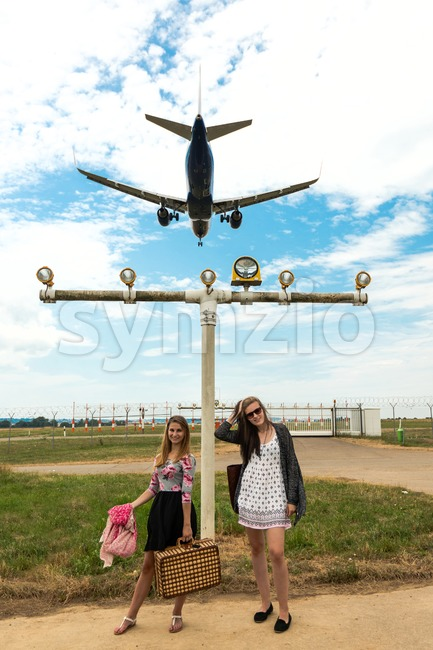 Two girls hitchhiking a plane Stock Photo
