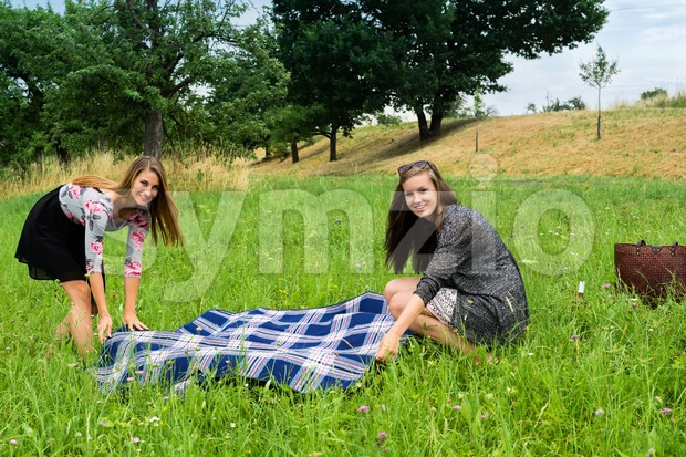 Two girls  spreading a blanket for picnic Stock Photo