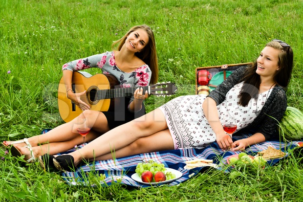 Two girls with guitar during picnic Stock Photo