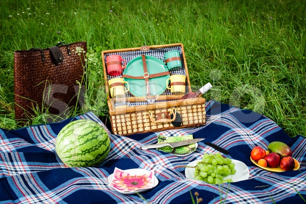 Picnic blanket and basket Stock Photo