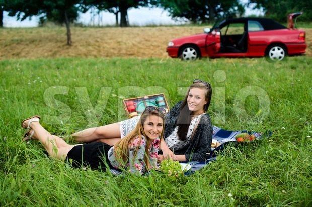 Best friends - two attractive young girls are having a picnic, dressed casual lying on the lawn in summer and ...