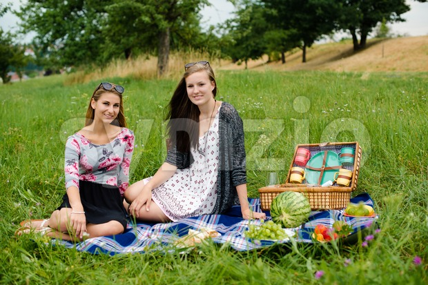 Best friends - two attractive young girls are having a picnic, dressed casual sitting on a blanket on the lawn ...