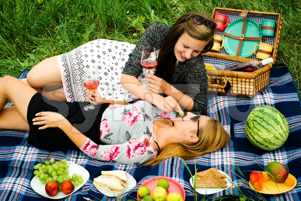 Best friends - two attractive young girls are having a picnic, dressed casual lying on the lawn in summer. One ...
