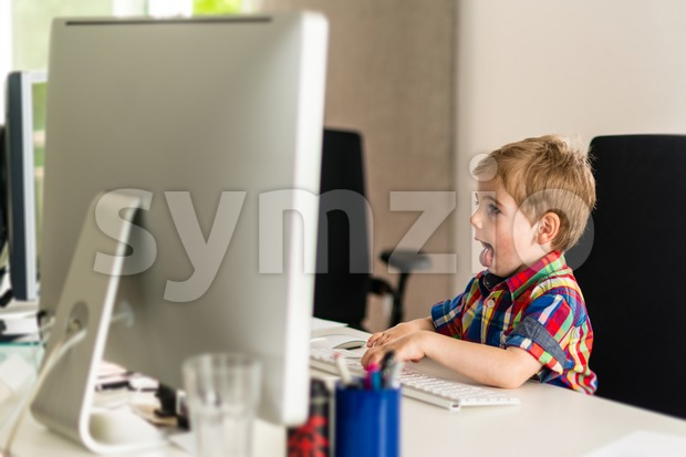 Little boy plays with computer Stock Photo