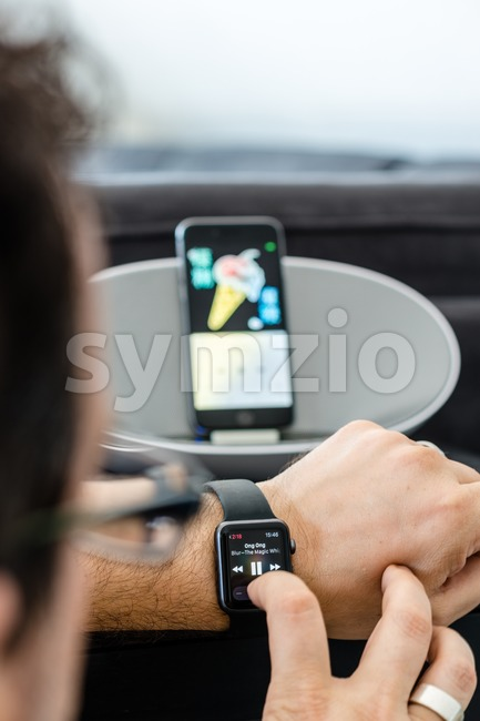 Apple Music - a man is controlling the music in his living room using the Apple Watch with his iPhone in a loudspeaker in the background Stock Photo