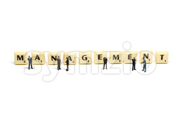 Management - Letters being surrounded by miniature figures Stock Photo