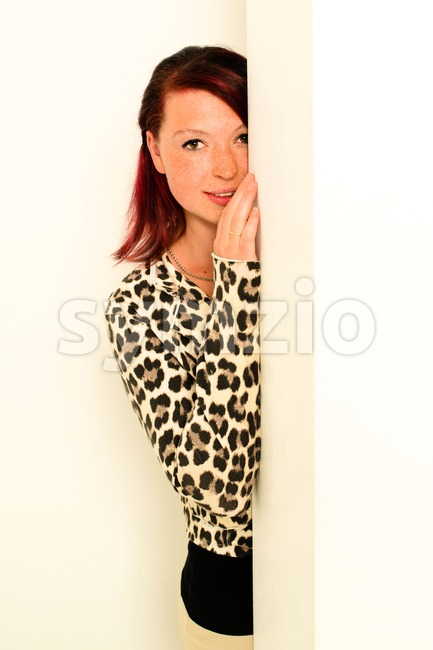 young woman peeking around the wall Stock Photo