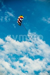 modern and colorful kite flying in blue sky Stock Photo