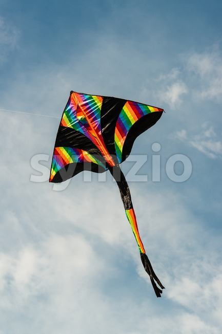 colorful kite flying in blue sky Stock Photo