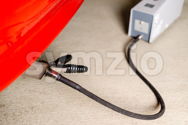 Sensor device measuring exhausts of a car in garage Stock Photo