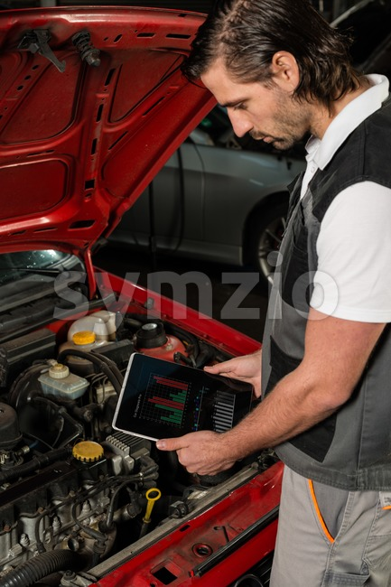 Close-up of a car mechanic using digital tablet in a garage, the tablet displaying (faked) diagnosis data