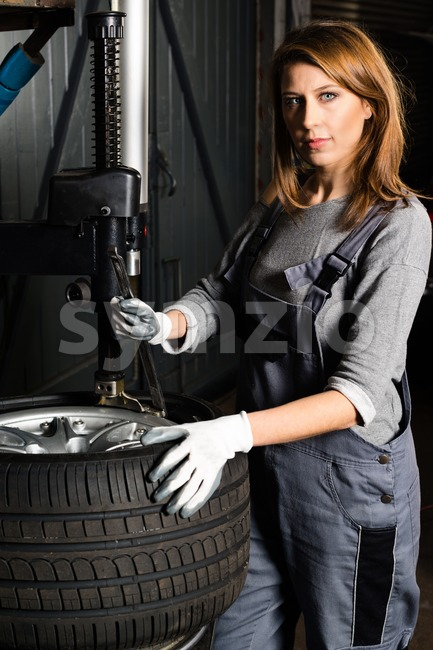 Young trainee changing  car tyre Stock Photo