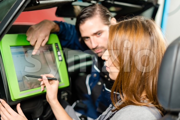 Auto mechanic is guiding a female trainee in checking the car performance with a digital device. Concept for the fact ...