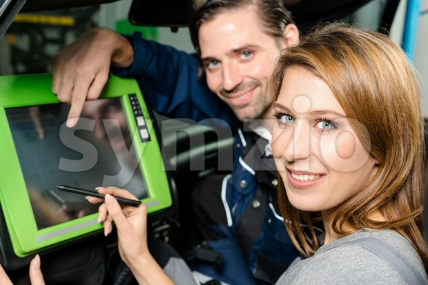 Auto mechanic is guiding an attractive female trainee in checking the car performance with a digital device. Concept for the ...