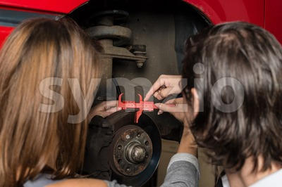 Auto mechanic and female trainee changing a car tyre in garage Stock Photo