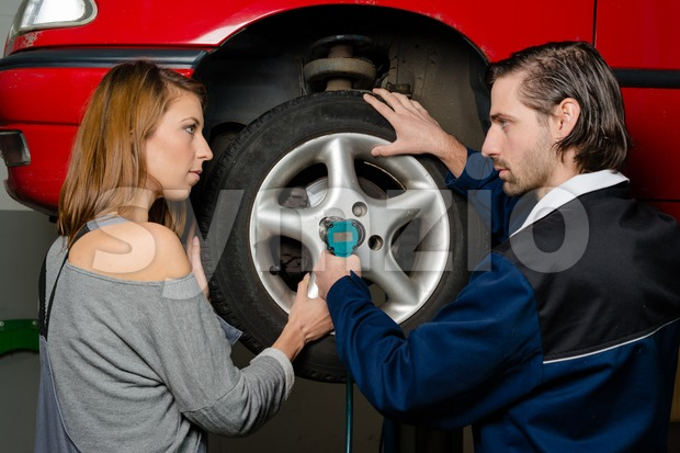 Women in male-dominated professions: Auto mechanic is guiding a female trainee in changing the tyre of a car in a ...