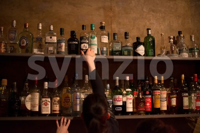 Waitress and bar shelves full of alcoholic beverages bottles Stock Photo