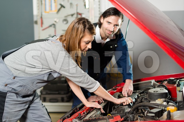 Auto mechanic guiding a female trainee in garage Stock Photo