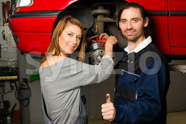 Auto mechanic and female trainee in garage Stock Photo