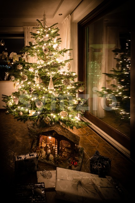 Beautifully decorated Christmas tree with nativity scene, presents and reflection