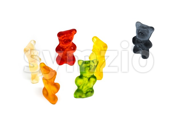 Social exlusion concept: Colorful gummy bears in group with one black bear being excluded - studio shot with shadows on ...