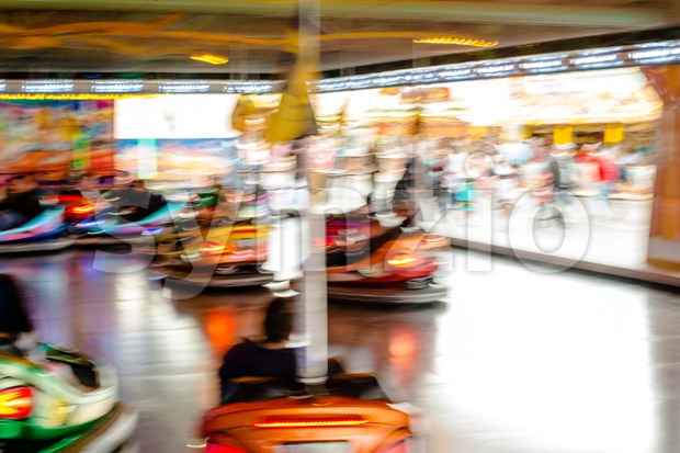 Bumper cars, people driving at the funfair. Motion blur