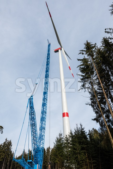 Construction of a wind turbine with large crane in wood glade