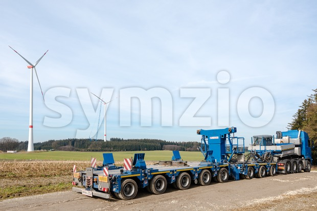 LAIMERING, GERMANY - FEBRUARY 27, 2016: Construction of wind turbines with a large trailer in the foreground and a large ...