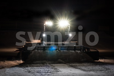 Snowcat preparing a slope at night Stock Photo
